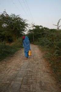 En av landsbykvinnene går den lange turen til nabolandsbyen for å hente vann til familien